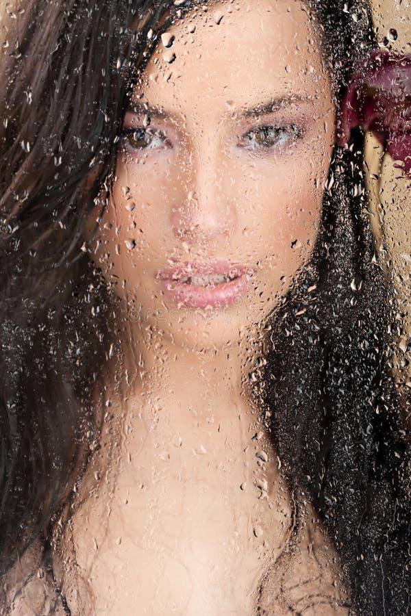 Fronte della donna dietro di vetro in pieno delle gocce dell'acqua immagine stock libera da diritti