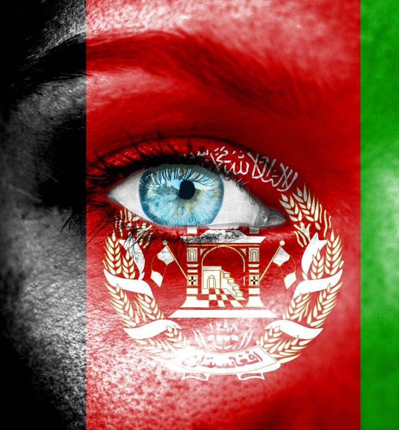 Fronte della donna dipinto con la bandiera di Afghanistan fotografia stock