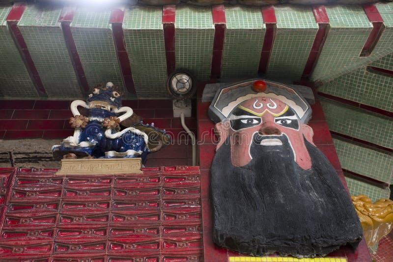 Fronte delle statue della divinità cinese sul portone di Tin Hau Temple o di Kwun Yam Shrine alla baia di rifiuto in Hong Kong, C immagini stock