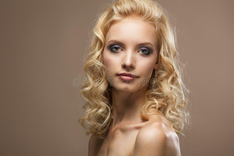 Fronte di bei capelli biondi ricci della giovane donna fotografia stock
