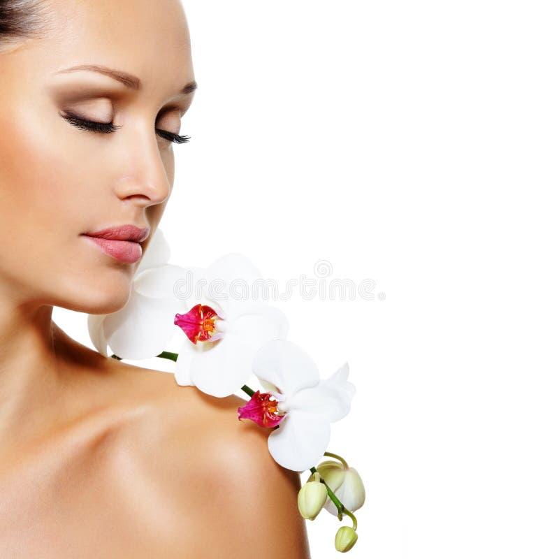Fronte di bella donna con un fiore bianco dell'orchidea immagini stock