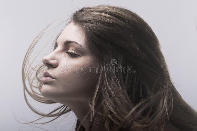 Fronte di bella giovane donna con il volo dei capelli fotografia stock
