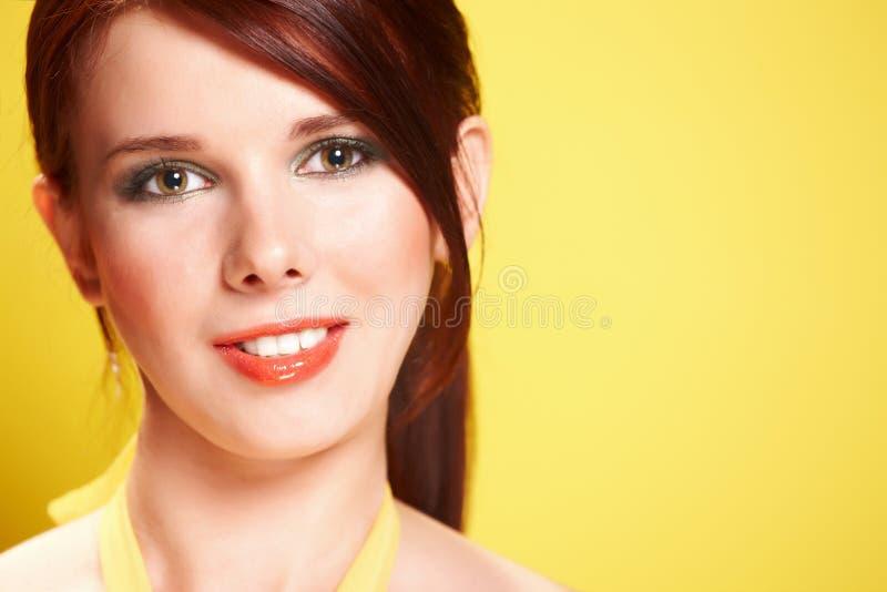 Fronte di bella giovane donna su priorità bassa gialla immagine stock
