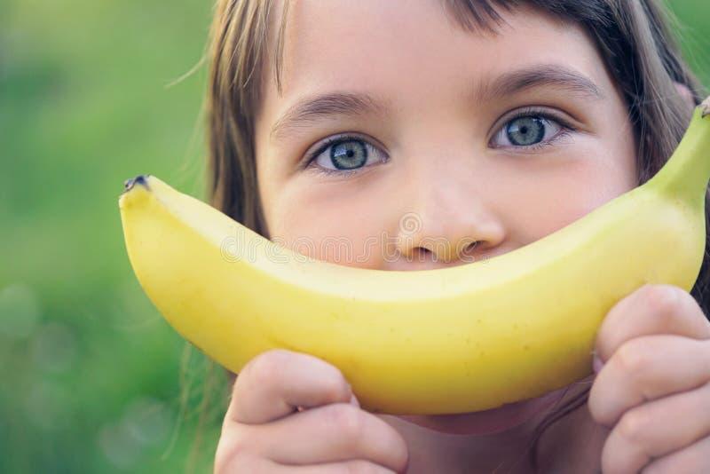 Fronte di bella giovane ragazza caucasica con il sorriso della banana sul fondo della natura fotografie stock