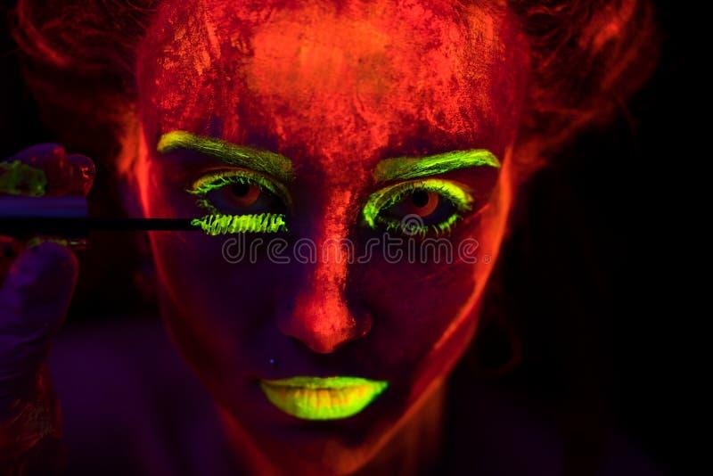 Fronte di bella giovane ragazza sexy con pittura ultravioletta sulla sua pelle che dipinge i suoi cigli con la spazzola in tintur fotografie stock libere da diritti