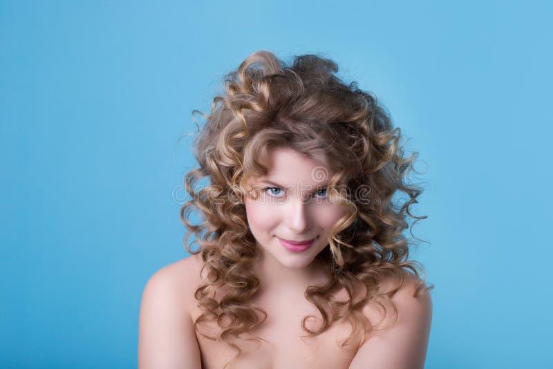 Fronte di bella ragazza con trucco su un fondo blu fotografia stock