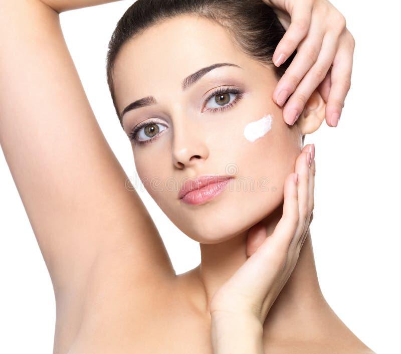 Fronte di bellezza della donna con crema cosmetica immagini stock libere da diritti