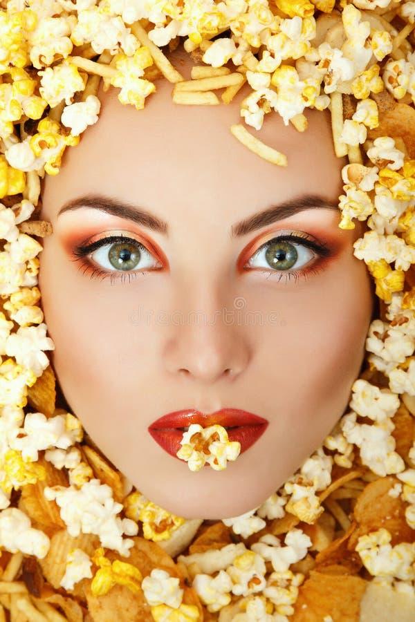 Fronte di bellezza della donna con unhealth che mangia la patata del popcorn degli alimenti a rapida preparazione fotografia stock libera da diritti