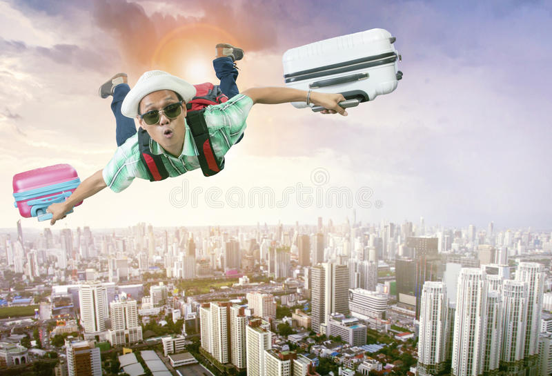 Fronte di felicità del volo di viaggio asiatico dell'uomo con due sedere dei bagagli immagini stock libere da diritti