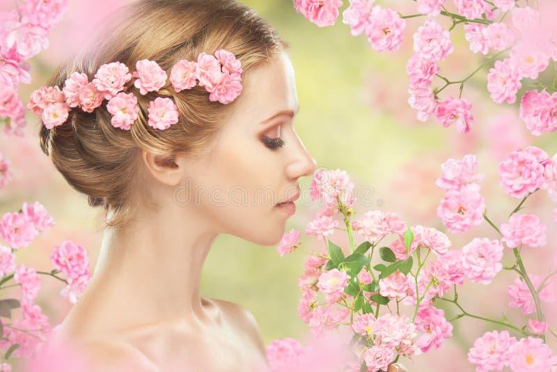 Fronte di giovane bella donna con i fiori rosa in suoi capelli immagine stock