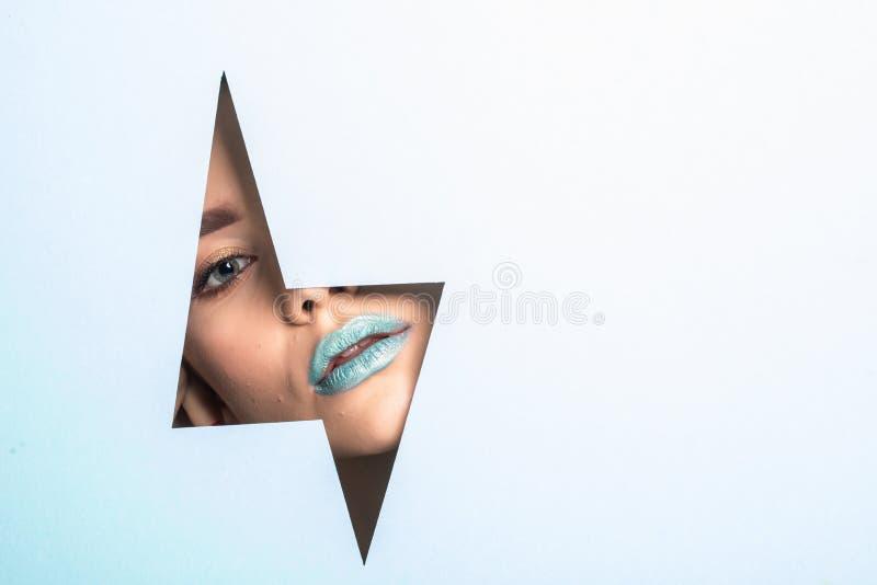 Fronte di giovane bella ragazza con un trucco luminoso e dei pari blu gonfi delle labbra in un foro in carta blu fotografia stock