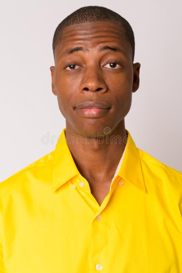 Fronte di giovane uomo d'affari africano calvo bello che porta camicia gialla fotografia stock libera da diritti
