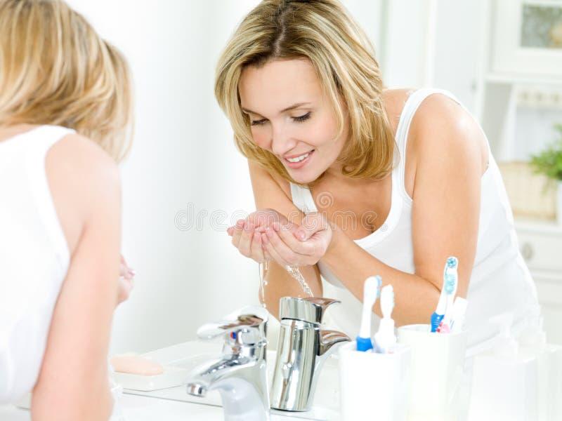 Fronte di lavaggio della donna con acqua fotografia stock