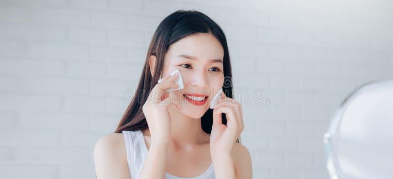 Fronte di pulizia della giovane donna asiatica di bellezza con il fronte della radura del cotone fotografia stock