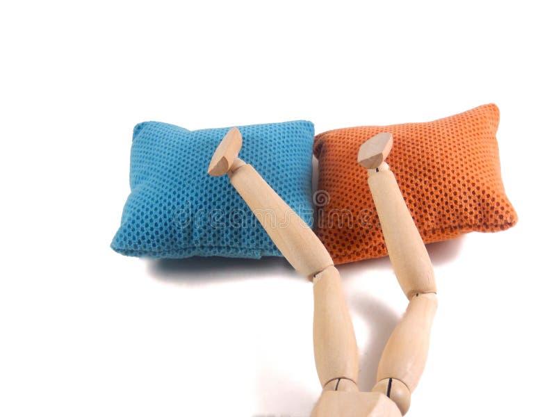 Fronte di sonno giù come piedi sopra i cuscini di letto, bambola di legno fotografia stock
