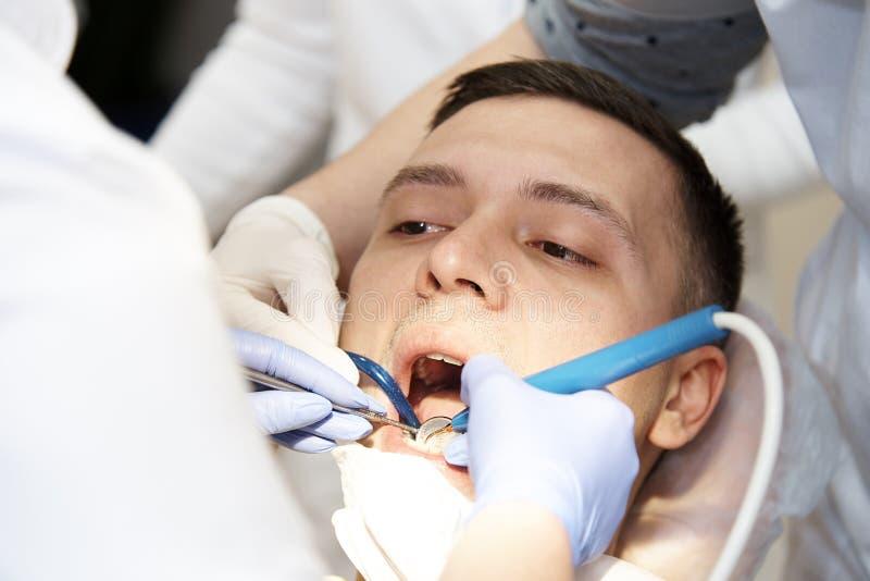Fronte di un giovane in una sedia dentaria con le mani del ` del dentista e di una bocca aperta una s con gli strumenti fotografia stock