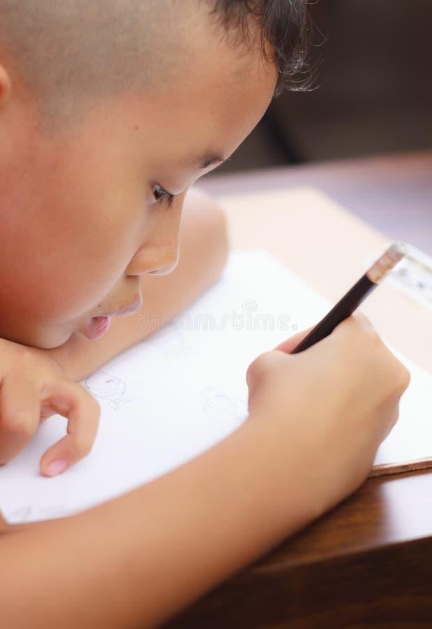 Fronte di un ragazzo asiatico che sta scrivendo sulla carta fotografie stock libere da diritti