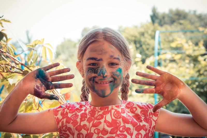 Fronte dipinto sorridente allegro del bambino del pittore creativo della ragazza che mostra a mani sviluppo luminoso di arte del  fotografie stock