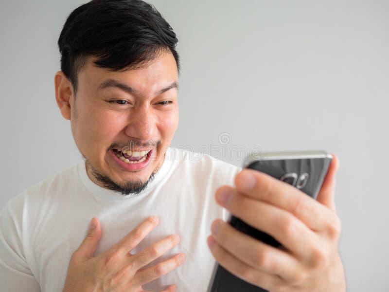 Fronte divertente di risata dell'uomo che guarda la parte divertente del videoclip in sociale nello smartphone fotografia stock