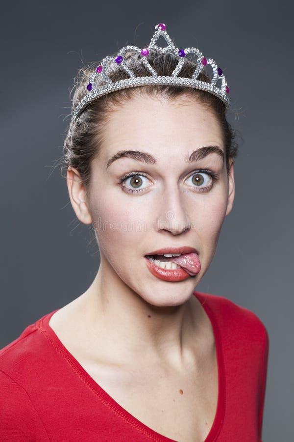 Fronte divertente per una giovane donna che posa come fuori la principessa della parete immagini stock libere da diritti