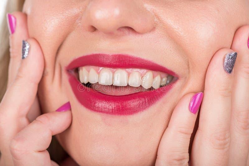 Fronte felice della donna con le labbra e le dita con le unghie polacche Tiro di foto dello studio fotografia stock