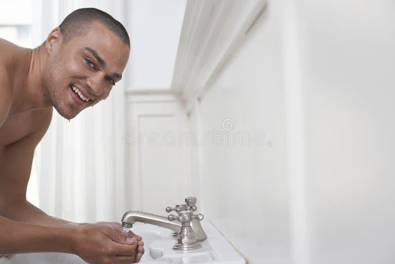 Fronte felice di lavaggio dell'uomo fotografie stock