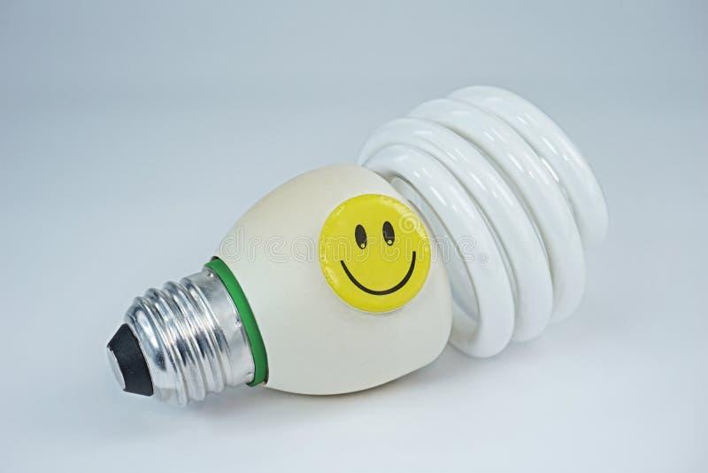 Fronte felice sorridente sulla lampadina economizzatrice d'energia su fondo bianco fotografie stock