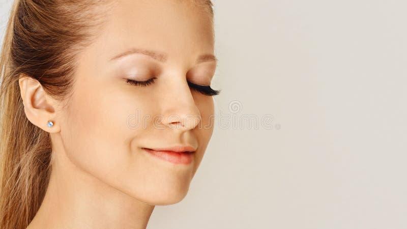 Fronte femminile con le sferze lunghe dell'occhio falso, prima e dopo effetto Estensioni del ciglio, trucco, cosmetici, bellezza immagini stock libere da diritti
