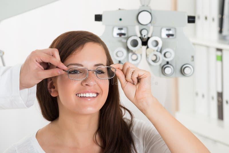 Fronte maschio del ` s della donna di Holding Eyeglasses On dell'ottico immagine stock libera da diritti