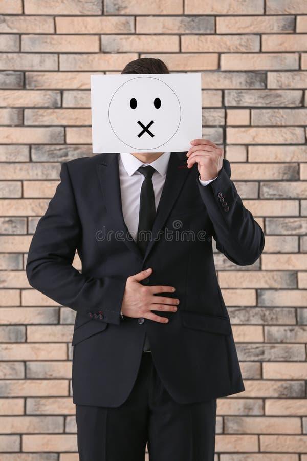 Fronte nascondentesi dell'uomo d'affari dietro il foglio di carta con l'emoticon tirato contro il muro di mattoni fotografia stock libera da diritti