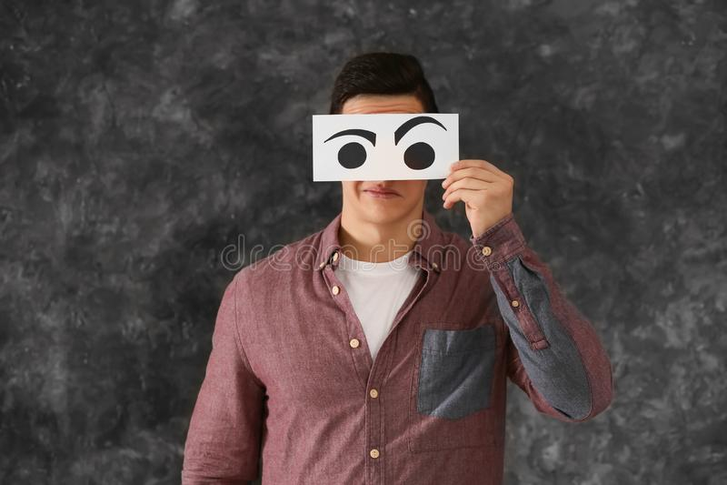 Fronte nascondentesi emozionale del giovane dietro il foglio di carta con gli occhi tirati su fondo grigio fotografia stock