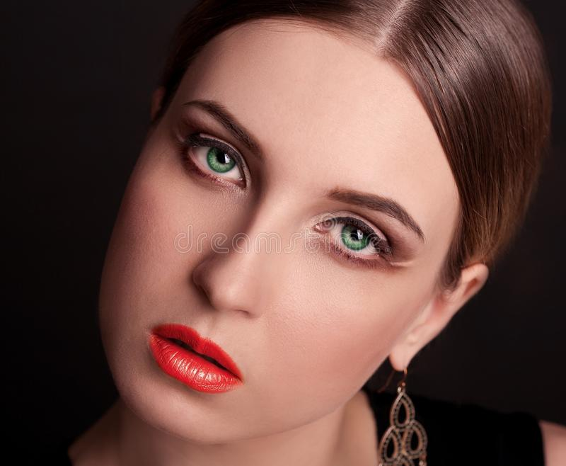 Fronte, occhi verdi, fondo nero, dai capelli, orecchini, labbra rosse immagine stock