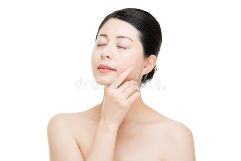 Fronte perfetto della pelle della donna del modello di tocco asiatico felice della mano immagini stock