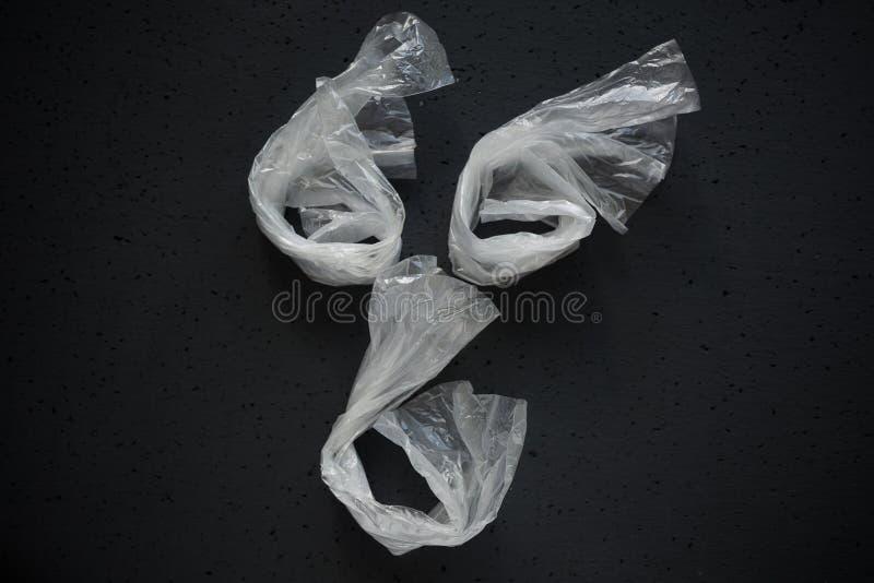 Fronte presentato dei sacchetti di plastica vuoti su un fondo scuro Il concetto di consumo ed inquinamento dell'ambiente fotografia stock libera da diritti