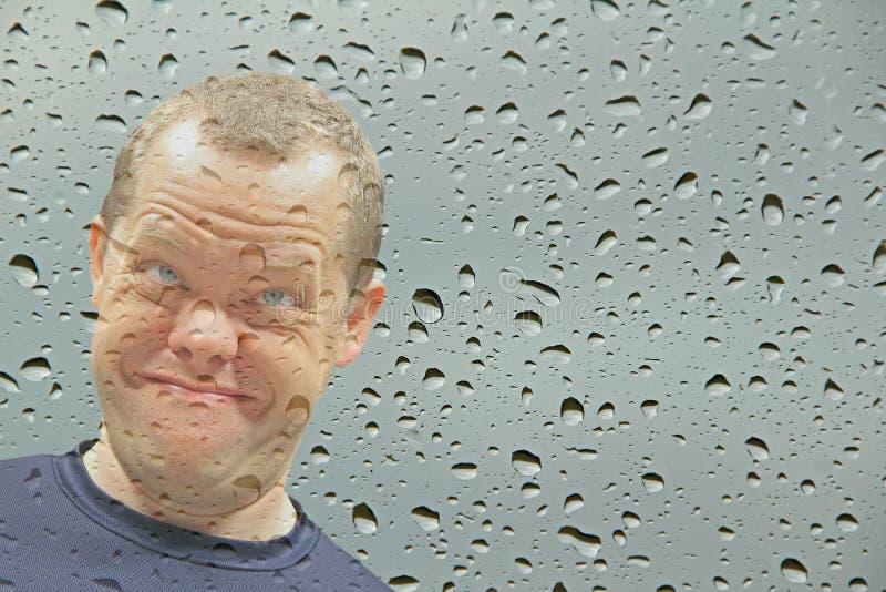 Fronte sorridente alla finestra bagnata fotografie stock