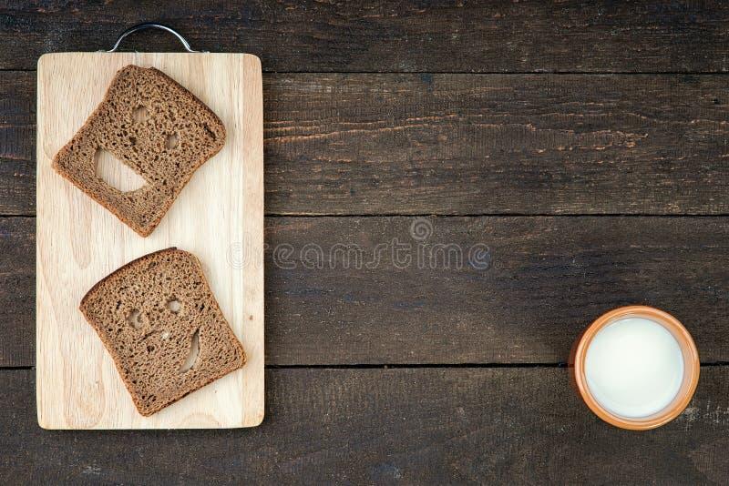 Fronte sorridente fatto da pane con la tazza del latte fotografia stock