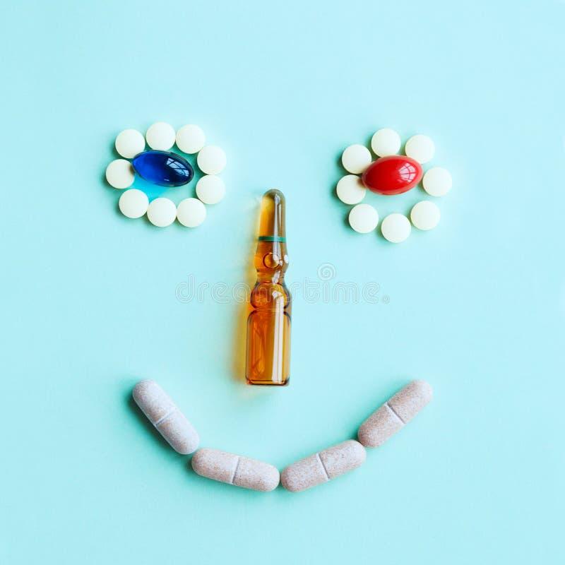 Fronte sorridente sveglio fatto delle compresse, delle capsule e di un'ampolla come naso fotografia stock