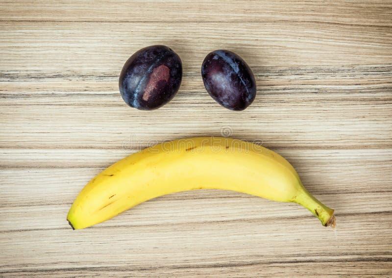 Fronte triste della banana e delle prugne, emozioni, tema della frutta fotografia stock libera da diritti