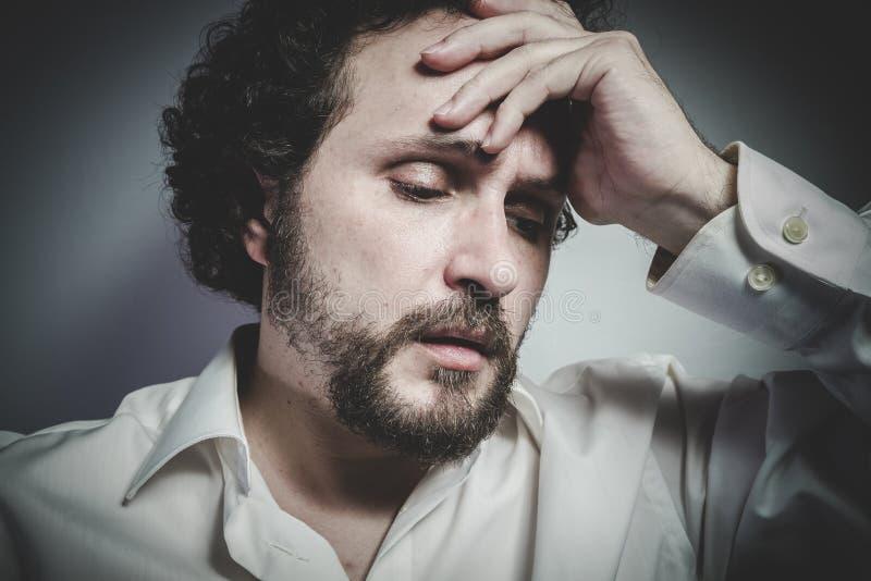 Fronte triste, uomo con l'espressione intensa, camicia bianca immagine stock