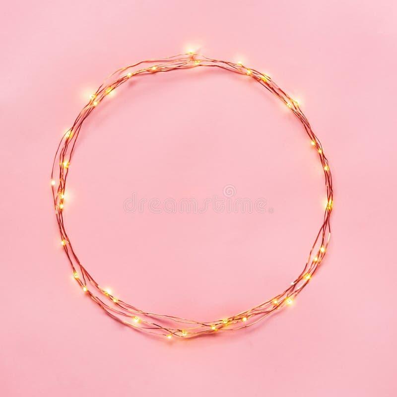 Frontera circular de la guirnalda de las luces de la Navidad sobre fondo rosado Endecha plana, espacio de la copia foto de archivo