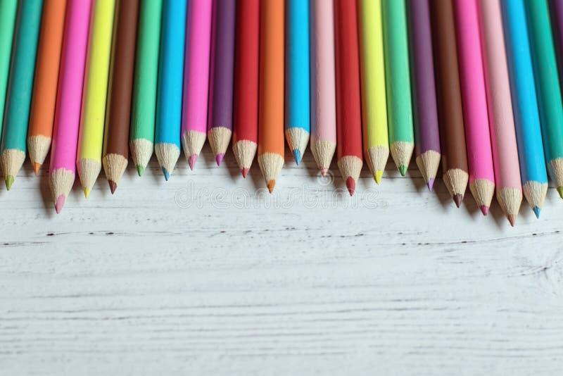 Frontera coloreada del lápiz en un fondo de madera, con el espacio de la copia fotografía de archivo libre de regalías