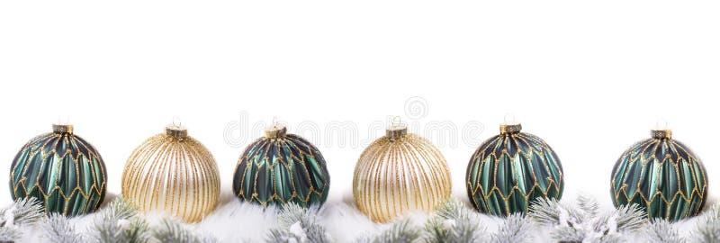 Frontera de bolas y de ramas de árbol verdes y de oro de abeto en el fondo blanco foto de archivo