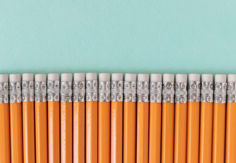 Frontera de lápices anaranjados con los borradores, en un fondo verde azul con el espacio de la copia fotos de archivo libres de regalías