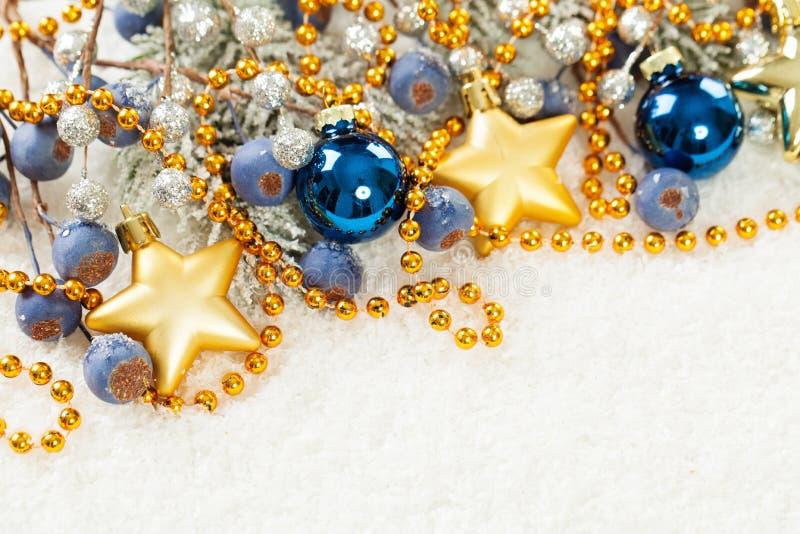 Frontera de la decoración de la Navidad con la estrella del oro y bolas de cristal azules en el fondo blanco de la nieve imágenes de archivo libres de regalías