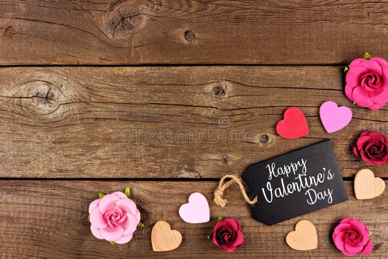 Frontera de la esquina feliz de día de San Valentín con la etiqueta, los corazones y las rosas del regalo contra la madera rústic fotografía de archivo