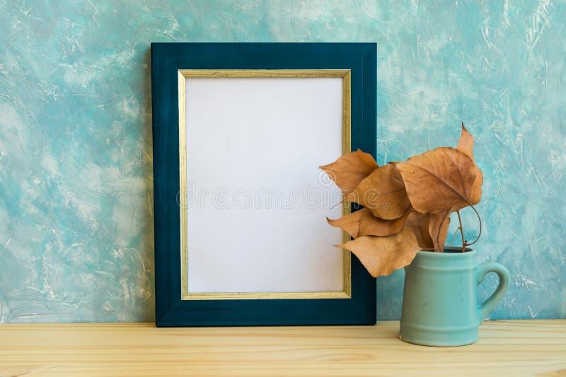 Frontera de la maqueta del marco del otoño, azul y de oro, rama de árbol con las hojas secas en echadas, fondo azulado del muro d fotos de archivo