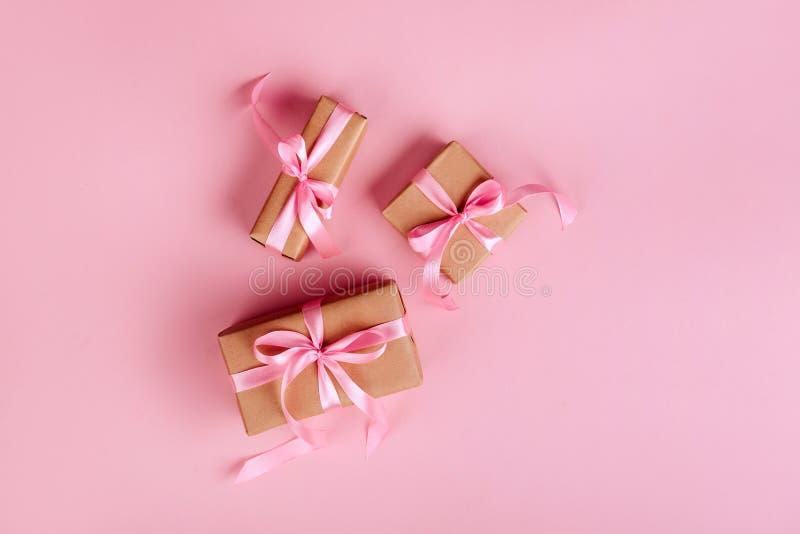 Frontera de la Navidad con las cajas de regalo, las bolas, la decoración y las lentejuelas en la opinión de sobremesa rosada fotografía de archivo libre de regalías