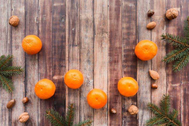 Frontera de la Navidad con las clementinas, las nueces y las ramitas del árbol de abeto foto de archivo