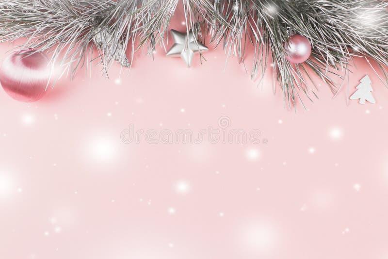 Frontera de la Navidad con las ramas del abeto, las bolas de la Navidad y los ornamentos de plata en el fondo del rosa en colores fotografía de archivo libre de regalías