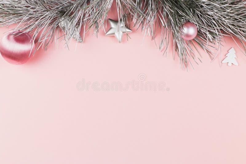 Frontera de la Navidad con las ramas del abeto, las bolas de la Navidad y los ornamentos de plata en fondo del rosa en colores pa foto de archivo